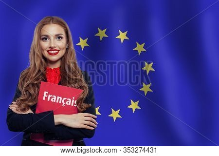 Happy Woman Student With French Book Against The European Union Flag Background. Book With Inscripti