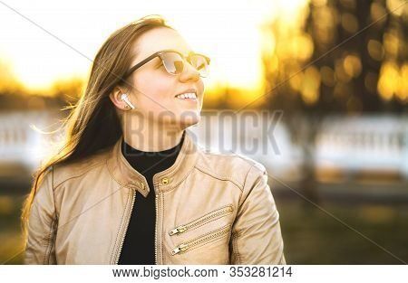 Wireless Headphones, Earbuds. Woman Listening To Music With Earpods In A Park. Happy Young Lady Smil