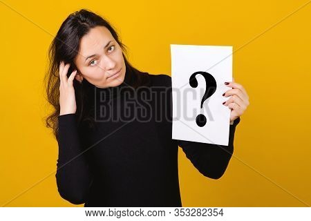 Young Woman Holding A Question Mark Over Yellow Background. Card With Question Mark Symbol. Women Qu