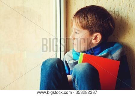 Sad Boy Sitting On Window Shield. Kid Looking Out The Window. Thoughtful Child Near Window. Sad Chil