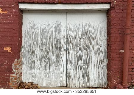 A Pair Of Faded White Painted Locked Shipping And Receiving Dock Doors On A Back Alley Red Brick War