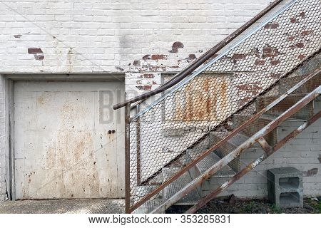 An Alley Warehouse Loading And Receiving Door With Rusted Stairs To Office