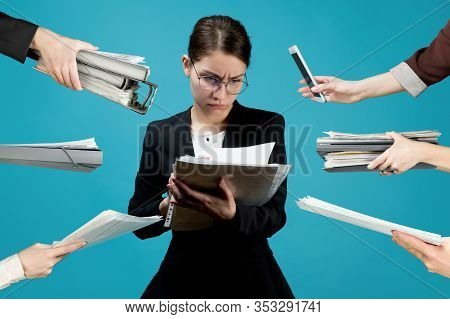 A Young Business Woman In A Strict Suit Carefully Scans Documents, At This Time Many Hands Hold Out