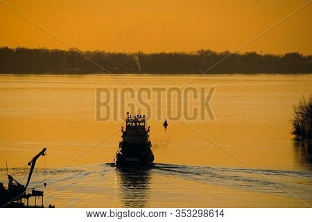 Silhouette Of A Riverboat Sailing On A River At Sunset