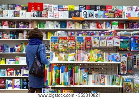 Minsk, Belarus - January 27, 2020: Rear View Of A Woman Choosing A Book On A Shelves In A Book Shop