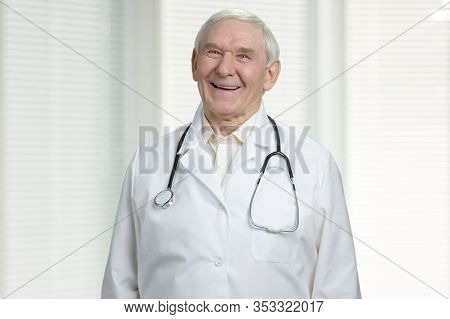Old Cheerful Doctor Is Laughing. Male Senior Wrinkled Physician With Stethoscope. Windows With Jalou