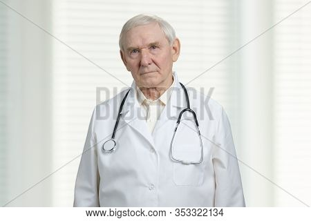 Gloomy Male Senior Doctor Portrait. Frowning Surgeon With Stethoscope In Windows With Jalousies Back