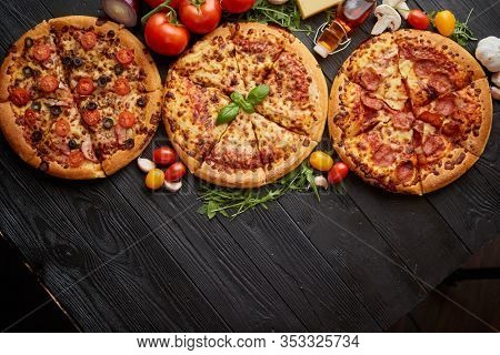 Freshly served, three various pizzas placed among tasty ingredients. Top view. Black wooden background with copy space for text.