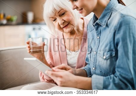 Young Lady And Her Grandmother Watching Video On Digital Tablet