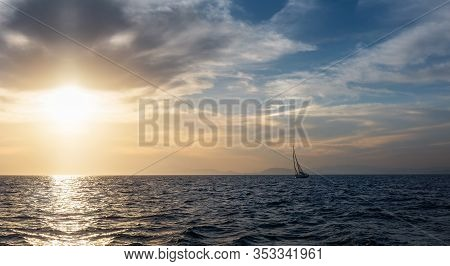Silhouette Sail Boat Gliding In Open Sea At Sunset. Tilted Monohull In The Evening. Luxury Summer Ad