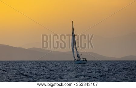Sail Boat In Open Sea At Golden Hour In Evening. Mountains Silhouette In Background. Summer Adventur