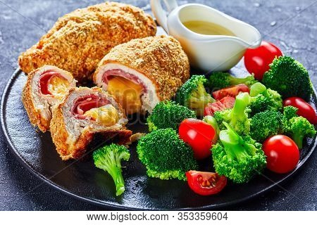 Chicken Cordon Bleu Baked In Oven With Ham And Cheese Stuffing Served On A Black Plate With Steamed