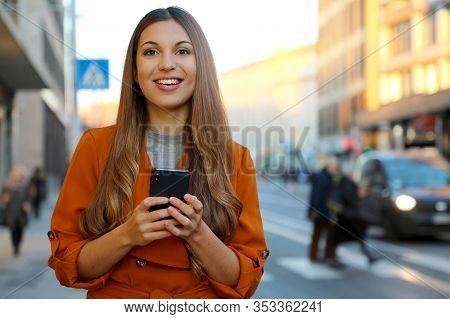 Happy Beautiful Young Woman Looking At Camera And Holding Mobile Phone Outdoor With Blurred People O