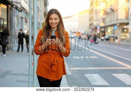 Portrait Of Beautiful Smiling Woman Walking In City Street Texting On Mobile Phone With Blurred Back