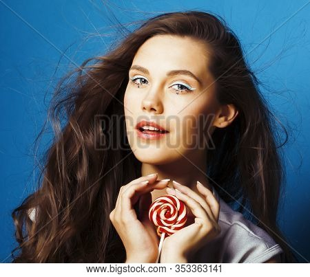 Young Pretty Adorable Brunette Woman With Candy Close Up Posing On Blue Background, Like Doll Makeup