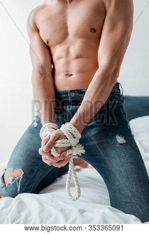 Cropped View Of Submissive Man Tied With Rope In Bedroom