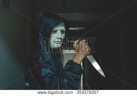 Murder, Kill And People Concept - Criminal Or Murderer In Black Wearing A White Mask Holding Knife I