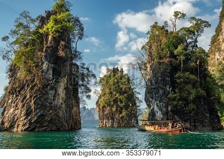 Wooden traditional thai longtail boat on Cheow Lan lake in Khao Sok National Park, Thailand