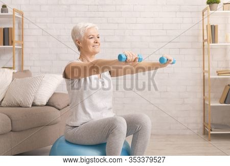 Active Retirement. Senior Woman In Sportswear Exercising With Dumbbells On Fitball At Home, Empty Sp