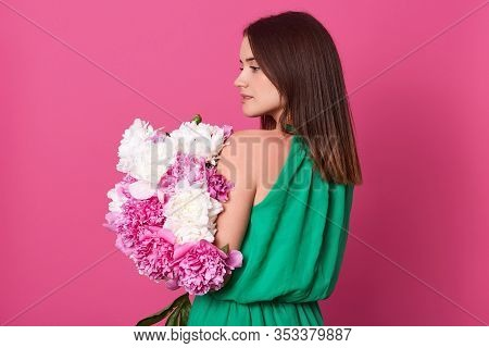 Side View Of Brunette Girl Holding Bouquet With White And Rosy Peonies, Posing Isolated Over Rosy Ac
