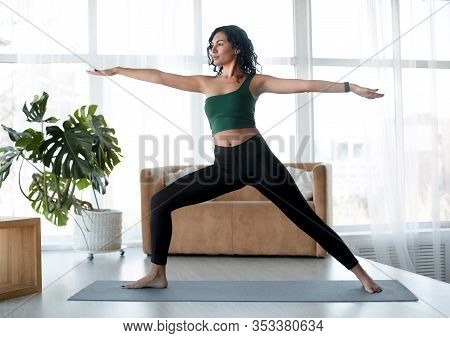 Home Fitness Concept. Attractive Hispanic Woman Doing Morning Yoga Exercises Indoors. Warrior Pose