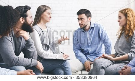 Mentor Psychologist Talking To Group Members At Therapy Session In Rehab, Giving Advices And Sharing