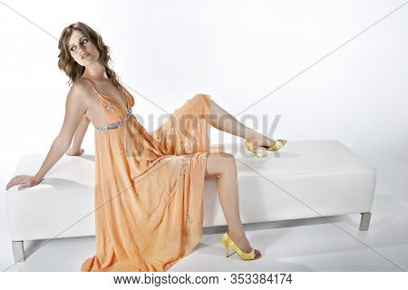 Cute Young Woman Like A Barbie Wear A Peach Dress And Yellow Heels, Sitting On A White Sofa In A Stu
