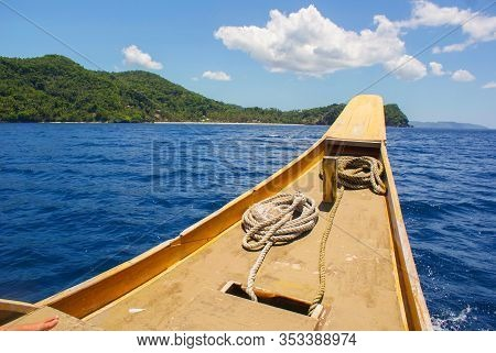 The Nose Of A Wooden Boat With Ropes On A Background Of Blue Sea And Green Hills.