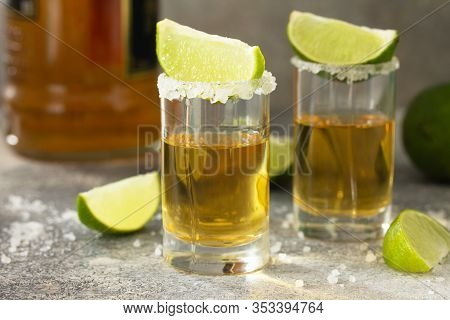 Gold Tequila. Mexican Gold Tequila Shot With Lime And Salt On A Stone Light Concrete Worktop.