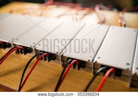 Close-up Metal Ac-dc Power Supply With Wires Lie On Wooden Table In Anticipation Of Further Installa