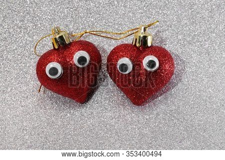 Two Big Red Hearts With Eyes On Glittery Silver Color Background