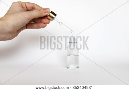 Hyaluronic Acid Drop Falls From Cosmetic Pipette On White Background, The Dropper Glass Bottle Mock-