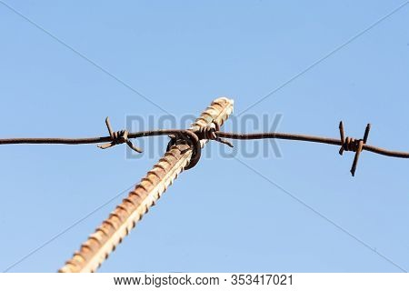 The Barbed Wire Is Stretched Over Supports Made Of Rusty Steel Reinforcement. Photographed On A Fon