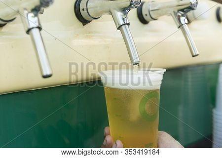 Bartender Pouring From Tap Fresh Beer Into The Plastic Cup.