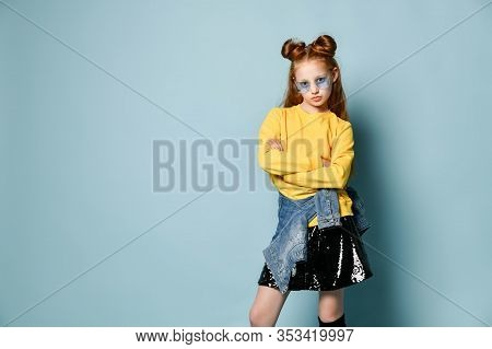 Cool Red-haired Teenager Girl Fashion Trendsetter In Smoked Glasses, Yellow Sweatshirt And Black Ski