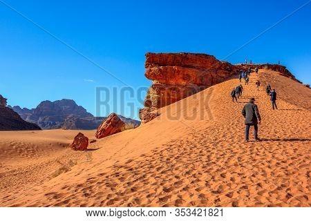 Aqaba, Jordan - Jan 5, 2020: People Climb The Dunes In Wadi Rum Desert At The Top Of Red Rock. Valle