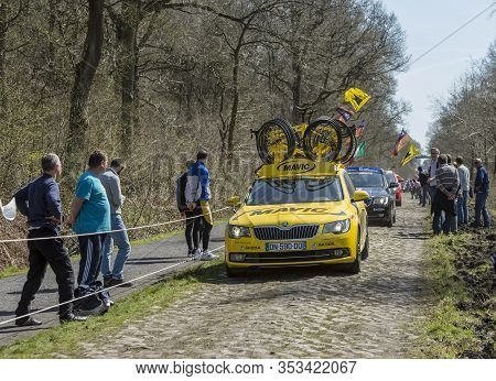 Wallers,france - April 12,2015: The Yellow Technical Car Of Mavic Driving On A Cobblestone Road Duri