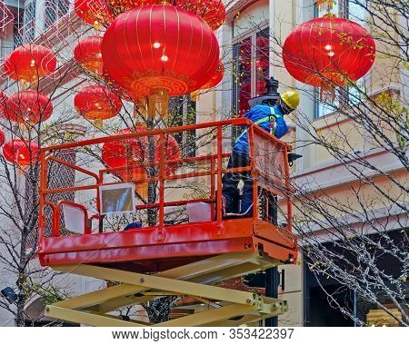Electrician On A Hydraulic Scissor Lift Is Serving A Street Lamp. Around The Decoration Of Chinese L