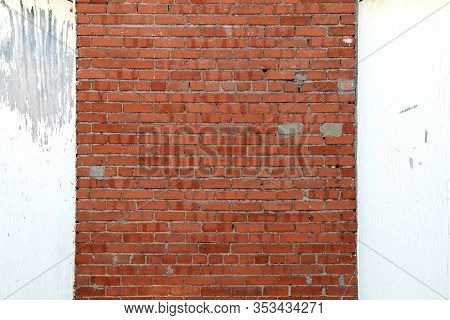 A Faded White Wood And Old Red Brick Garden Shed Exterior Wall