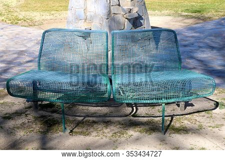 A Rusted Green Park Bench Round Nest To A Monument