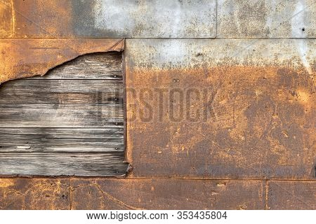 A Rusted Steel Metal Wall With Exposed Rotten Wood Board