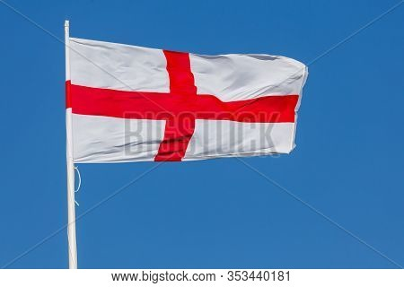 St. George Flag Of England Flying In The Wind On A Flagpole With Blue Sky. Red Cross On White Backgr