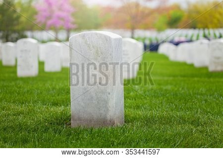 White Tombstone On The Lawn Of Military Cemetery In A Row Of Graves