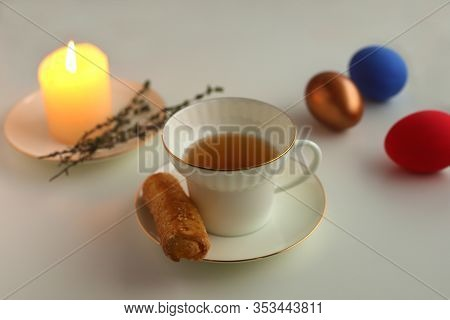Easter Colored Eggs Lie On A Saucer Next To A Burning Candle. White Cup With Tea And Cookies On A Sa