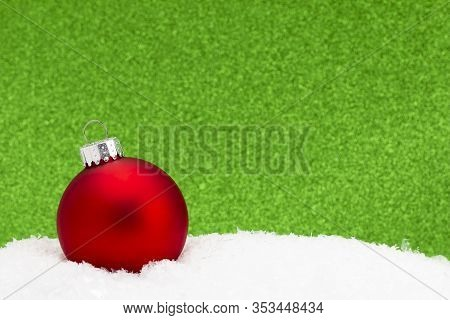 Christmas Ornament In The Snow With A Glittery Background