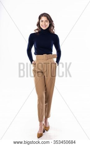 Happy Young Woman Looking At Camera While Standing At Isolated White Background