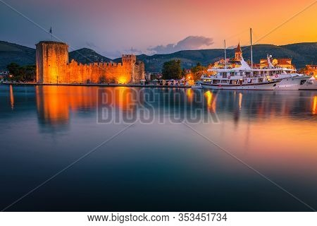 Trogir Harbor With Boats And Cityscape At Sunrise. Illuminated Kamerlengo Castle And Street Lights A