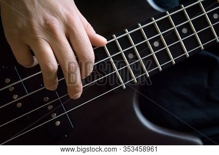 Bass Guitar Player Hand Closeup, Lesson And Practice Theme. Playing On Bass Electric Guitar, Live Mu