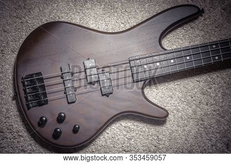 Bass Guitar With Four Strings. Popular Rock Musical Instrument. Top View Of Brown Electric Bass On C