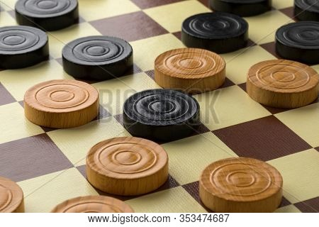 Draughts board or Checkers board with light and dark pieces close up